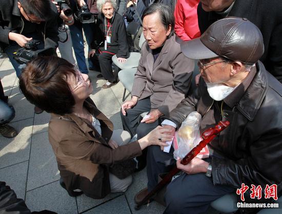资料图 来自日本铭心会南京访华团的团长松冈环(左)单膝跪地,在和南京大屠杀幸存者交谈。中新社发 泱波 摄
