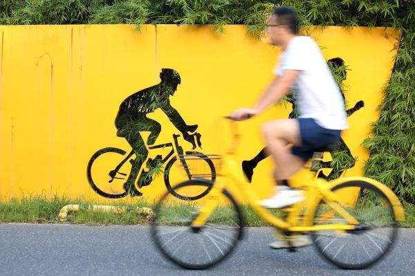 浙江嘉兴市民在中央公园内骑共享单车出行。新华社