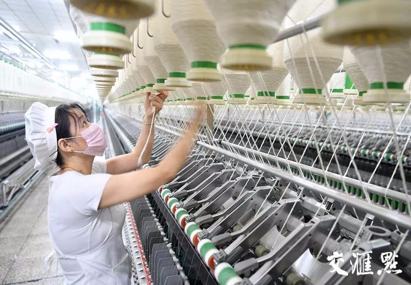 江阴一家纺织厂里,一位纺织女工正忙着包纱。交汇点记者 肖勇 宋峤 余萍摄
