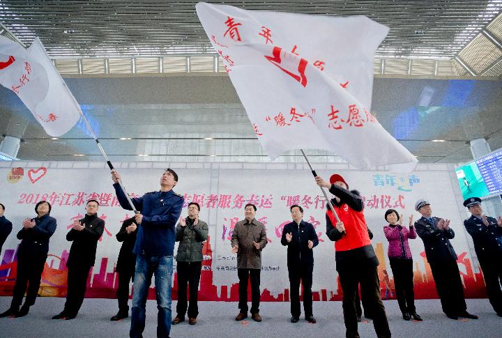 """团中央、团省委领导为2018年春运""""暖冬行动""""青年志愿者服务总队授旗。张炜 摄"""