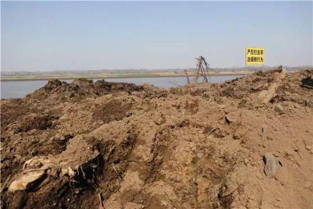 """铜陵上江村的倾倒点,工业垃圾堆满整段江滩,较相连江滩高出数米,上面竖着""""严厉打击非法倾倒行为""""的警示牌。新华社记者 曹力 摄"""