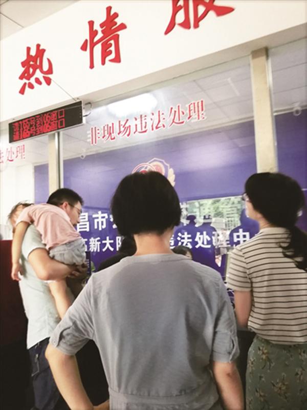 办事大厅里很闷热,市民背上衣服都被汗湿。本文图均为中国江西网 图