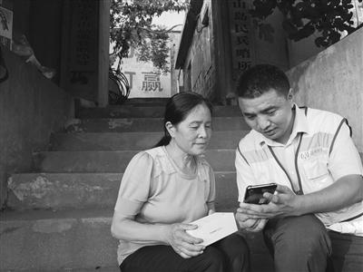 移动公司工作人员为英雄王继才的妻子展示手机网络。 杨恒国 杨泽华 摄
