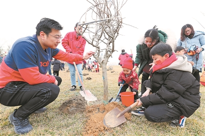 植树节前,家长带着孩子到公园植树。 司 伟 刘家献摄 视觉江苏网供图