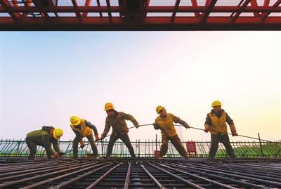 江西省南昌市洪都大道高架桥建设中,农民工兄弟们正齐心协力穿高架桥钢索。