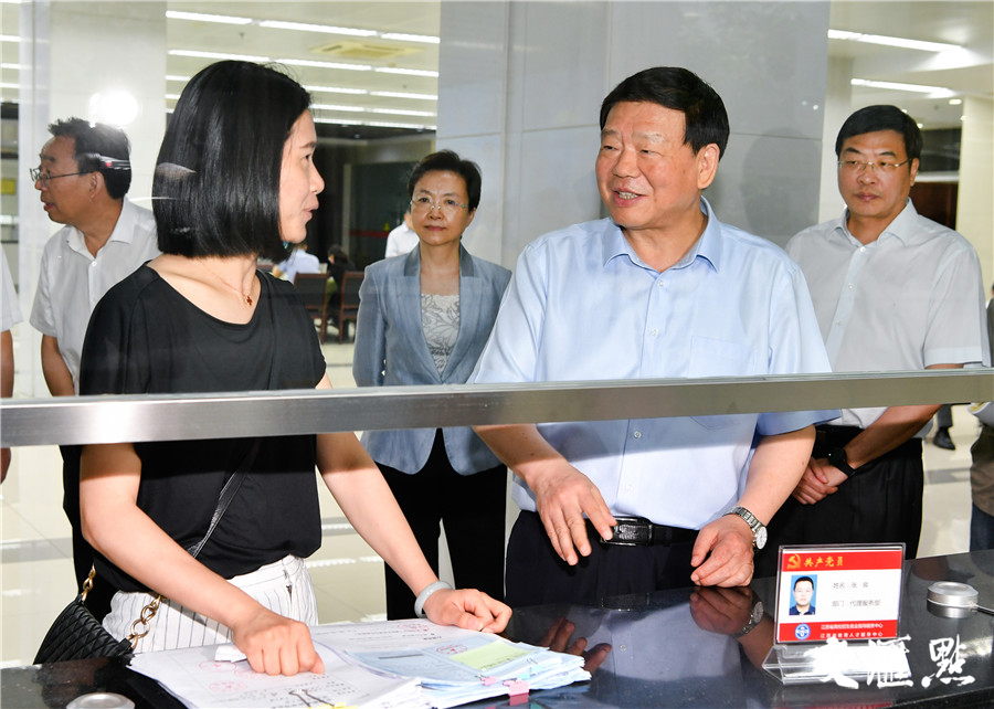 在江苏省高校招生就业指导服务中心,娄勤俭与正在窗口办理毕业生就业报到证的高校工作人员交谈交流。